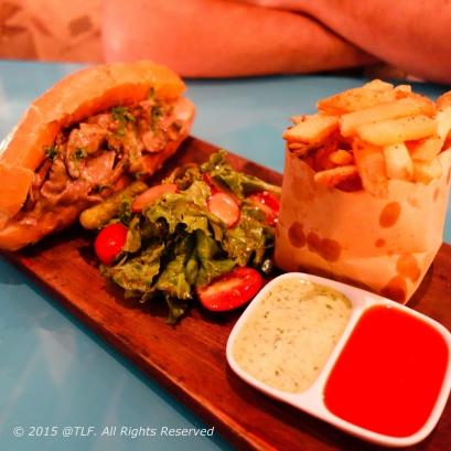 Philly cheesesteak sandwich : bánh mỳ kẹp steak thái mỏng và pho mát đun chảy (cơ bản), thêm 3 loại nấm, kèm salad, khoai tây chiên, và sốt caper (nụ bạch hoa) aioli và tương cà quán tự làm.